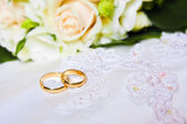 Wedding rings with bouquet — Stock Photo