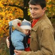 Father holding his son in baby carrier — Stock Photo