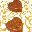 Mouthwatering chocolates in a heart-shaped on a colored background — Stock Photo