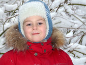 Portrait of a boy in winter clothing against the backdrop of snow — Stock Photo