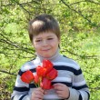 Portrait of a boy with a bouquet of red tulips — Stock Photo