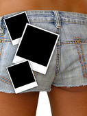 Young girl in denim shorts and photo frames — Stock Photo