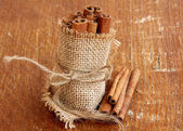 Cinnamon on wooden background — Stock Photo