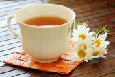 Herbal tea with camomile on a wooden table — Stock Photo