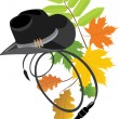 Cowboy hat and whip on the autumn background - Stok Vektör