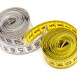 Yellow and white measuring tapes - Stock Photo