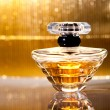 Stock Photo: Bottle of perfume with reflection on gold