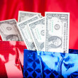 Birthday gift with dollars on red background — Stock Photo