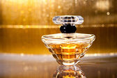 Bottle of perfume with reflection on gold — Stok fotoğraf