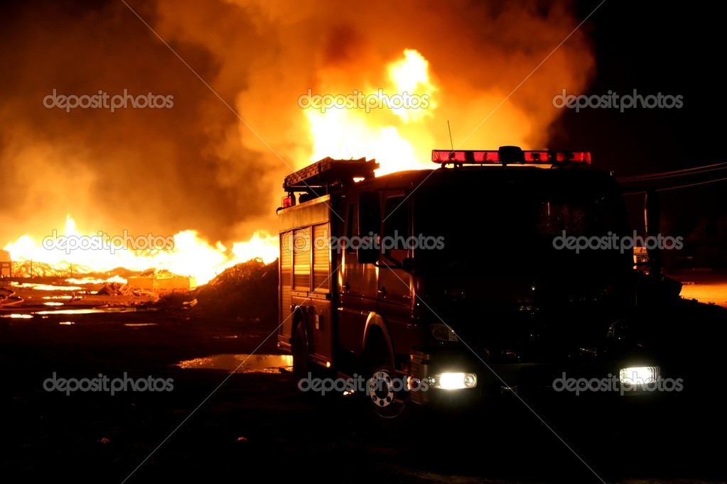 A firetruck in front of a blazing fire at night  Stock Photo #4661275