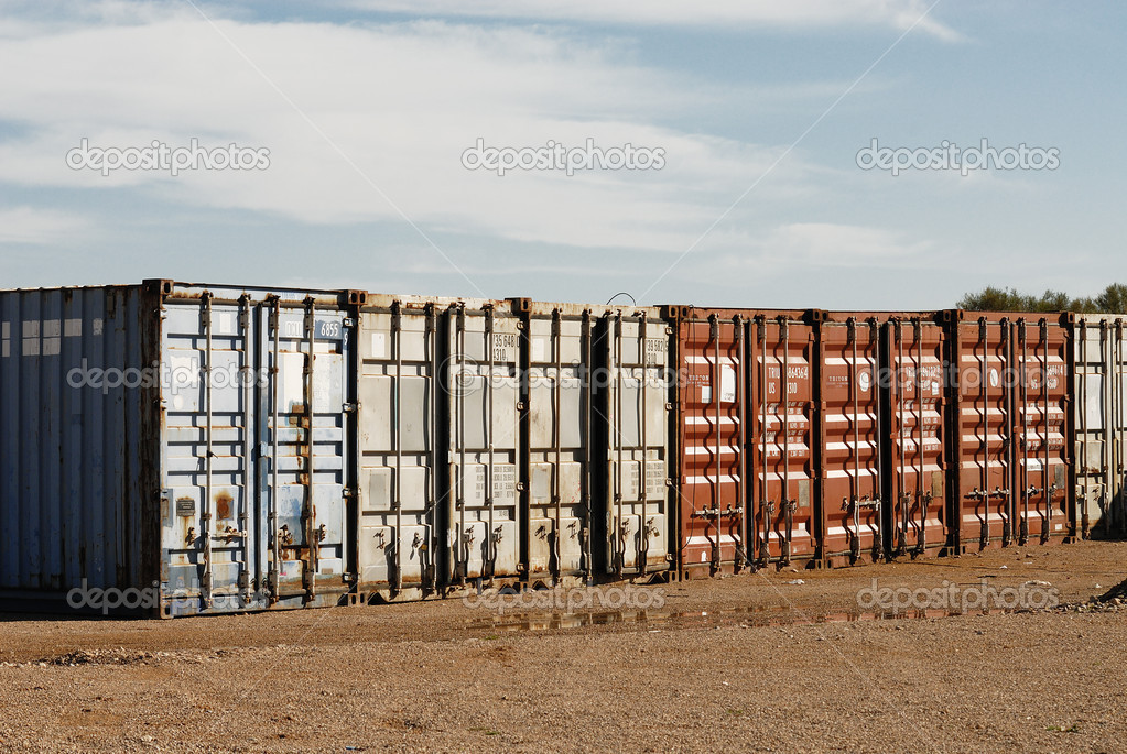 Stacked freight containers awaiting import/export at a commercial dockside.  Zdjcie stockowe #5011461