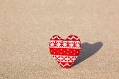 Red knitted heart on sea sand — Stock Photo