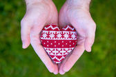 Man hands with red knitted heart — Stock Photo