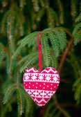 Knitting heart on fir-tree branch — Stock Photo