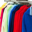 Multicolor sport shirts hanging in store — Stock Photo