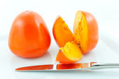 Two ripe persimmons and steel knife — Stock Photo