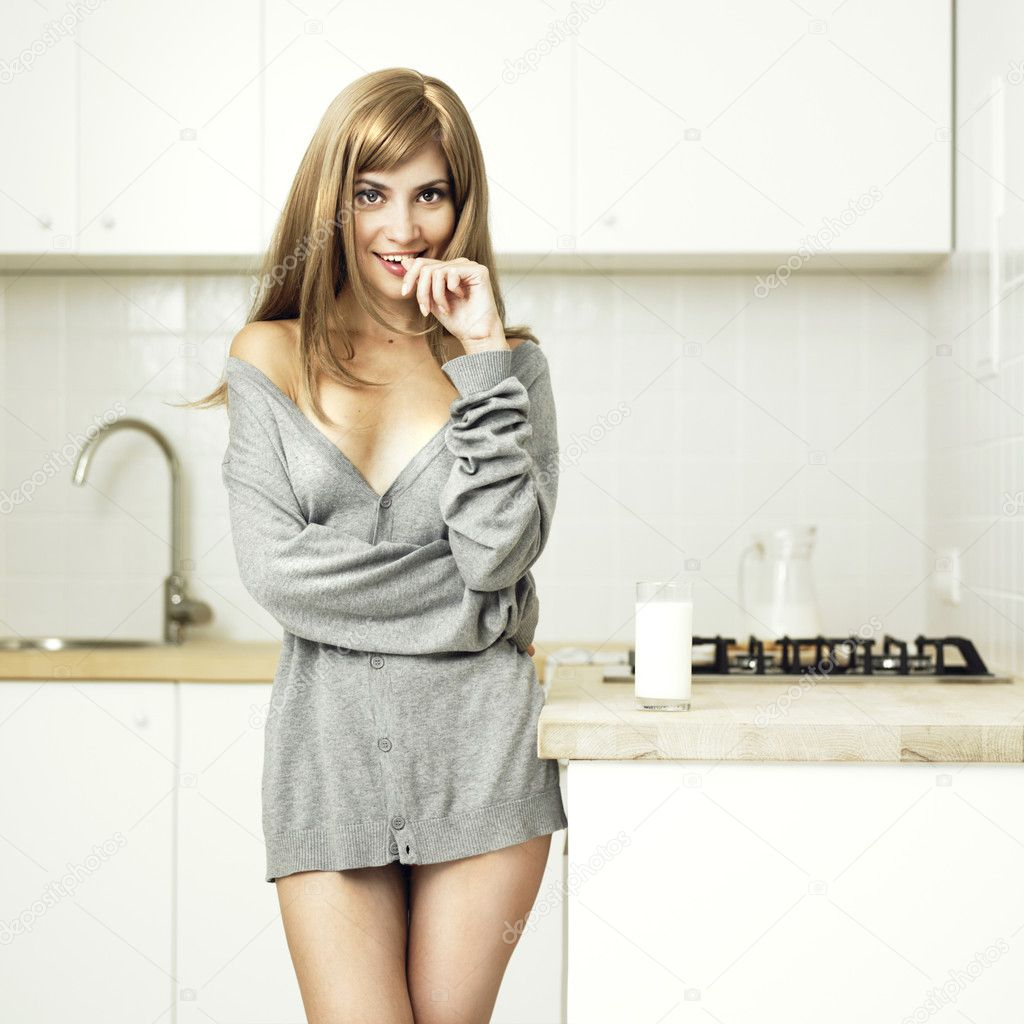 Beautiful girl with milk on the home kitchen — Stock Photo #4134863