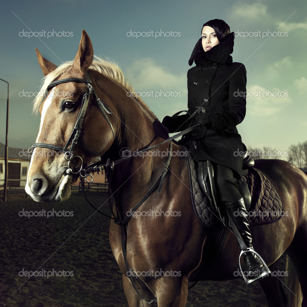 Elegant woman in a black coat riding on a brown horse — Stock Photo #4134880