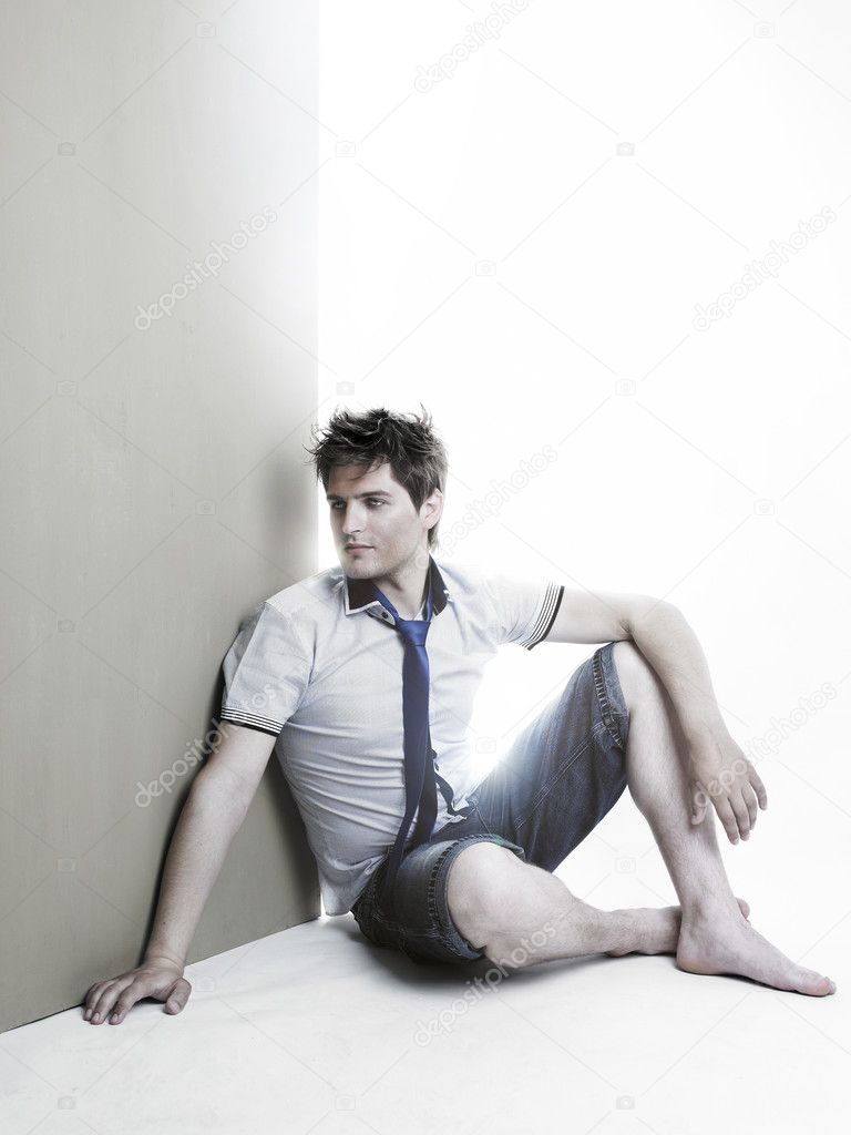 Portrait of a handsome young man sitting against the wall — Stock Photo #4499566