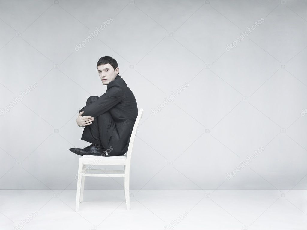 Surreal portrait of a man sitting on a white stool — Stock Photo #4802721
