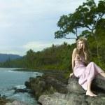 Beautiful woman on a rocky seashore — Stock Photo
