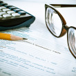 Stock Photo: Eye glasses on accounting book with pencil and calculator