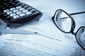 Eye glasses on an accounting book with pencil and calculator — Stock Photo