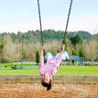 Stock Photo: Happy little nine year old part Asigirl on swings at park