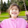 Happy little girl smiling on swing at park — Stock Photo #5107502