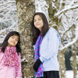 Two little girls standing by tree in fresh snow — Stock Photo #5107522