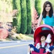 Teen girl pushing her little brother in stroller — Stock Photo