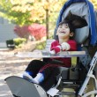 Stock Photo: Disabled boy in medical stroller outdoors