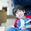 Stock Photo: Cute disabled boy with cerebral palsy smiling in stroller