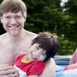 Father holding disabled son in pool — Stock Photo #5107623