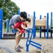 Stock Photo: Older brother helping disabled sibling play