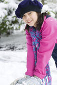 Beautiful twelve year old girl playing in the snow — Stock Photo