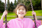 Happy little girl smiling on a swing at the park — Stock Photo