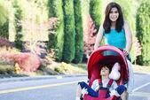 Teen girl pushing her little brother in stroller — Stock Photo