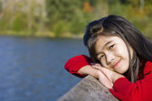 Little girl relaxing by lake — Stock Photo