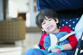 Cute disabled boy with cerebral palsy smiling in stroller — Stock Photo