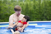 Father holding disabled son in pool — Stock Photo