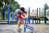 Older brother helping disabled sibling play — Stock Photo