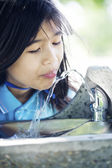 Girl drinking from fountain — Stock Photo