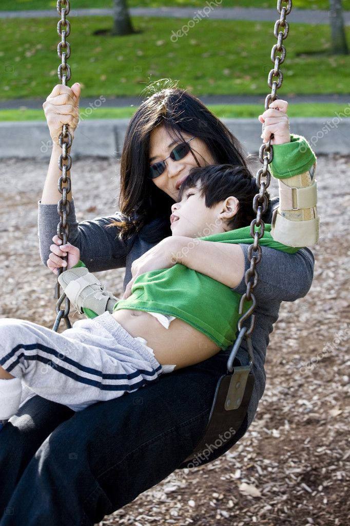 Mother swinging with her disabled son with cerebral palsy — Stock Photo #5107601
