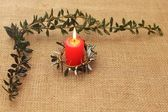 Frame from lighting candle and branches of holly tree — Stock Photo