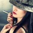 Beautiful smoking woman wearing hat — Stock Photo
