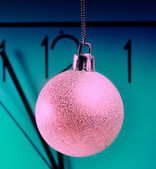 Clock and decorated ball over green — Stock Photo