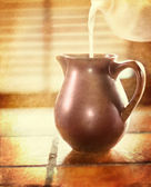 Milk pouring in a brown jug — Stock Photo