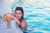 Beautiful girl drinking juice in the pool — Stock Photo