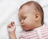 Little girl sleeping on a white towel — Stock Photo